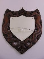 Lot 56 - A Chinese shield shaped wall mirror, the pierced hardwood frame carved with dragons, mirror A/F