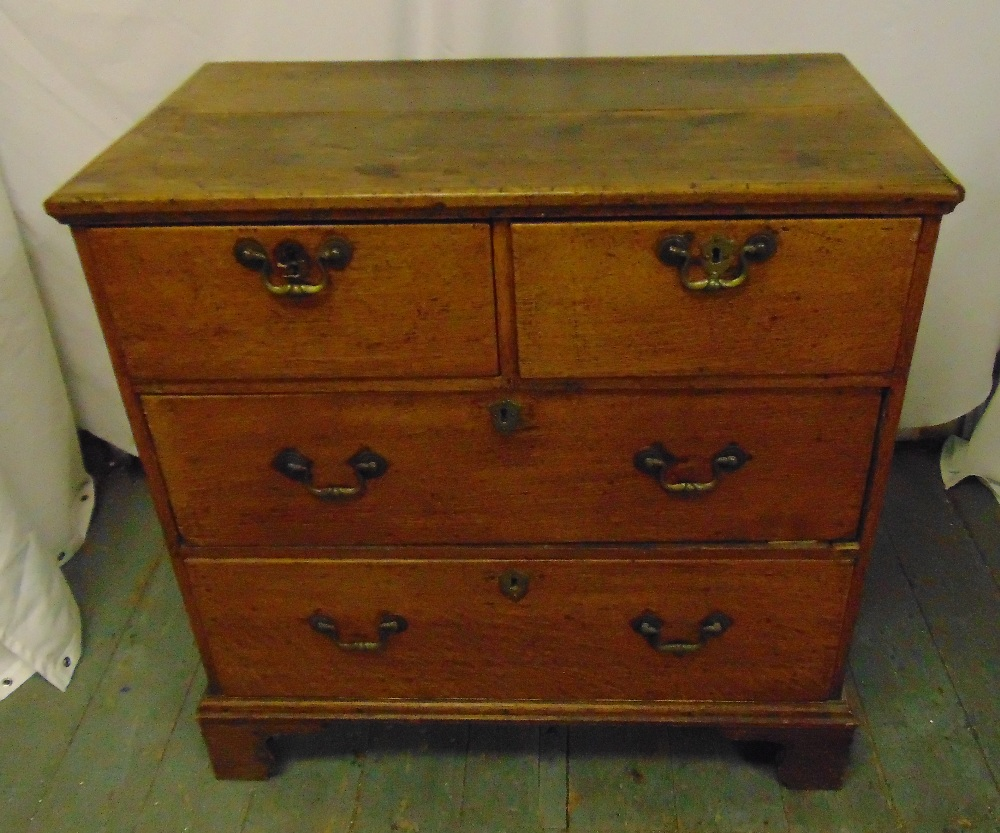 Lot 16 - A rectangular pine chest of drawers with brass swing handles on four bracket feet