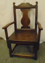 Lot 42 - An early 18th century oak chair with central splat, open arms and canted square legs