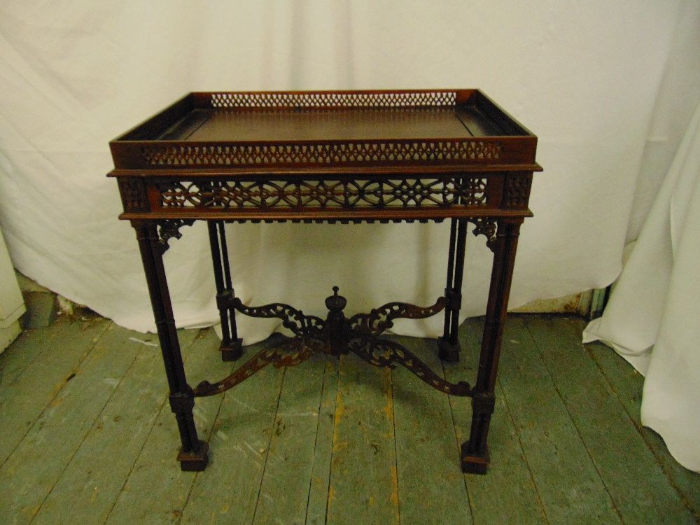 Lot 23 - An Oriental rectangular hardwood drinks table, scroll pierced gallery and sides on four stylised
