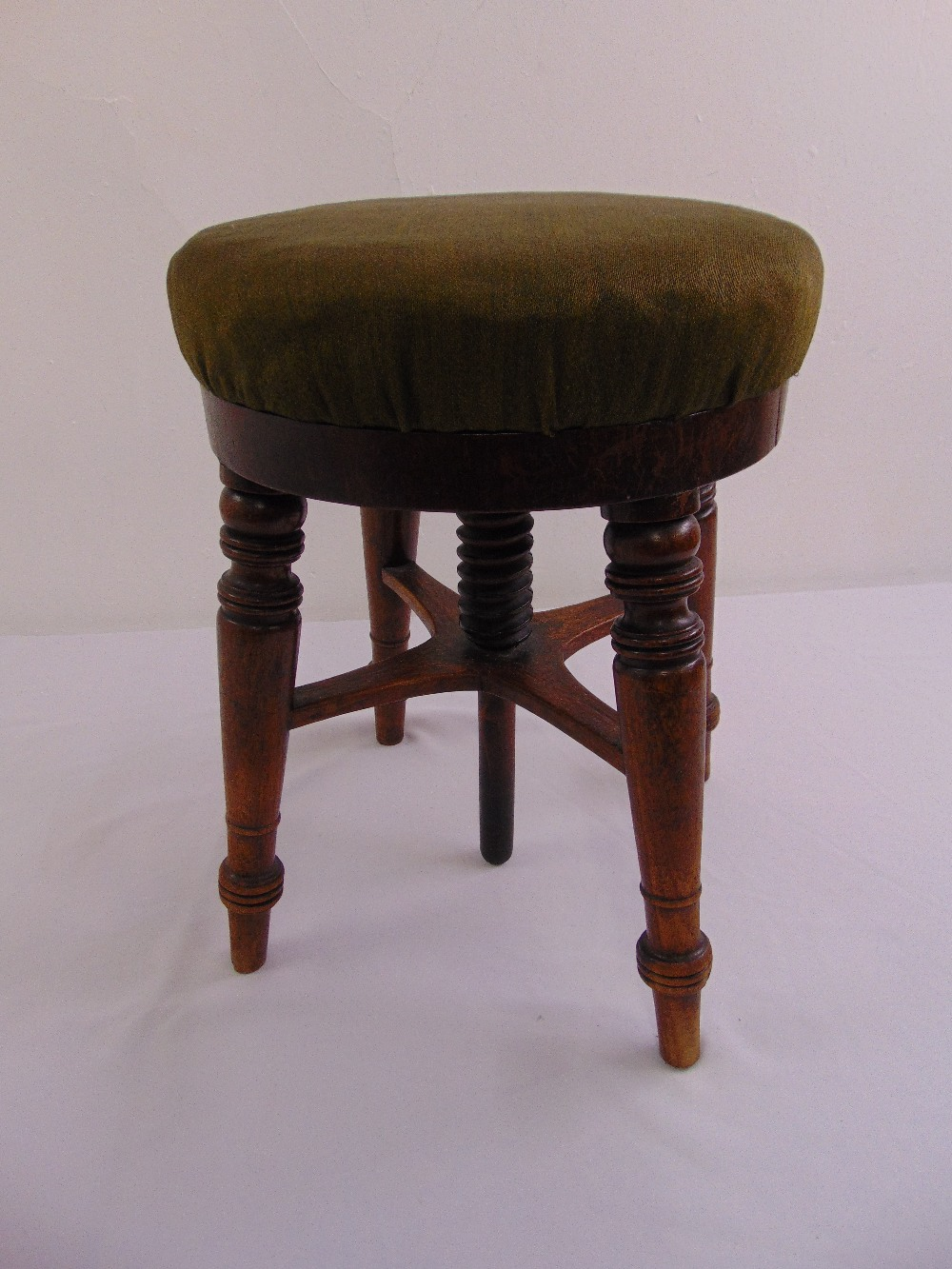 Lot 45 - An oak circular rise and fall piano stool on four turned legs