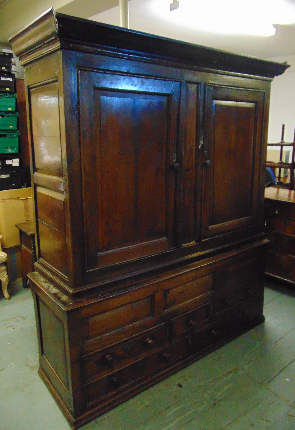 Lot 4 - An 18th century rectangular oak cupboard with hinged panelled doors, the plinth base with drawers