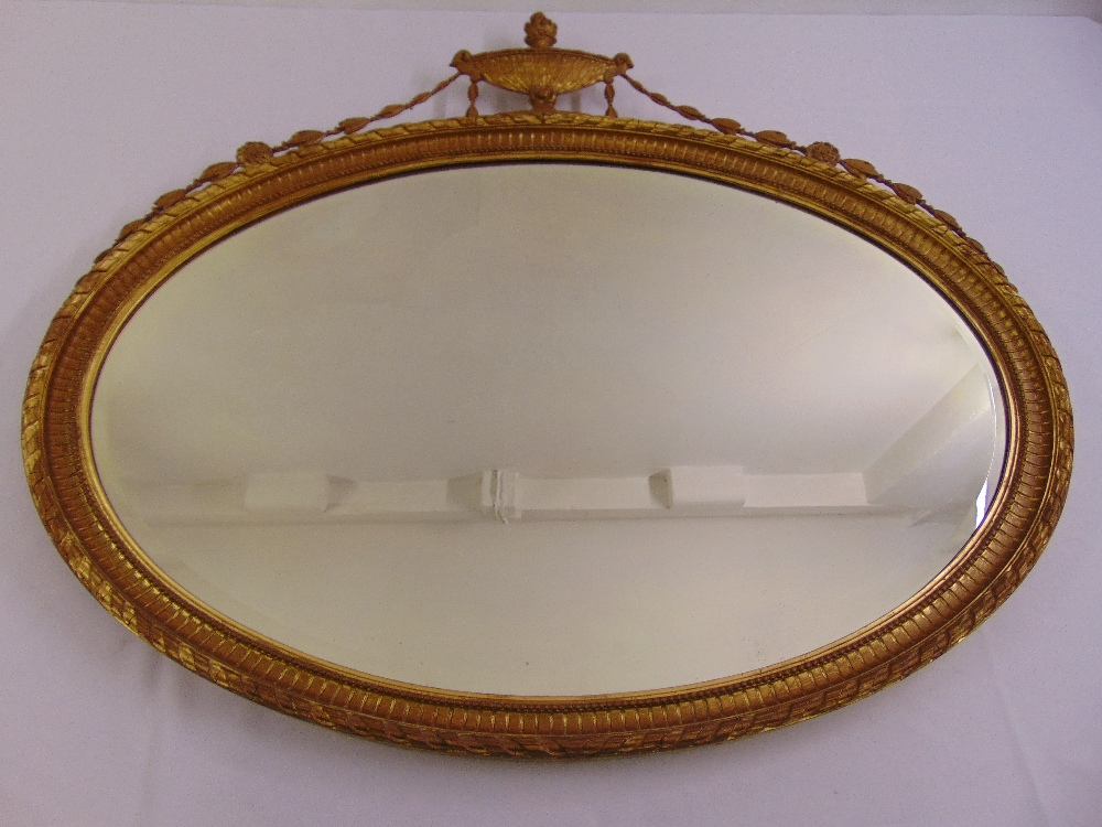 Lot 54 - A gilded neo-classical style oval mirror surmounted by an urn with husk swags