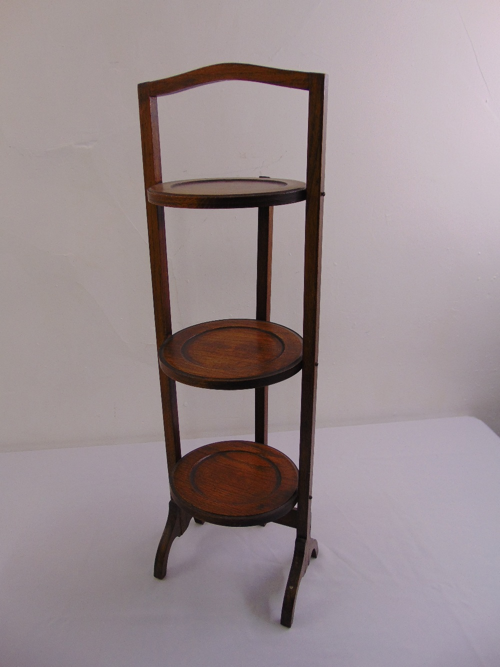 Lot 48 - An oak three tier plate stand