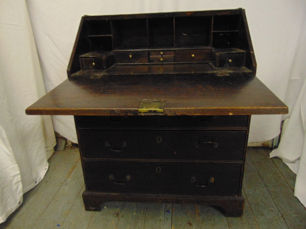 Lot 5 - A 19th century rectangular oak bureau, the hinged top above three drawers with brass handles, all on