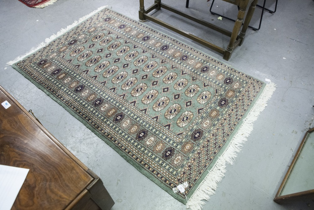 "Lot 15 - PAKISTAN BOKHARA RUG with two rows of guls on a green field, multiple border stripes, 5' x 3' 2"" ("