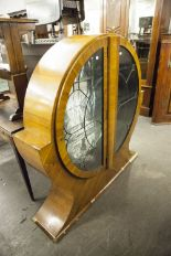 "Lot 31 - ART DECO WALNUT DISPLAY CABINET, of circular form with leaded glass doors, 50"" high, some losses"