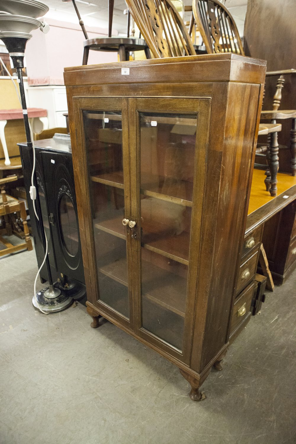 "Lot 32 - EARLY TWENTIETH CENTURY MAHOGANY TWO DOOR DISPLAY CABINET, with cabriole supports, 54 ½"" high"