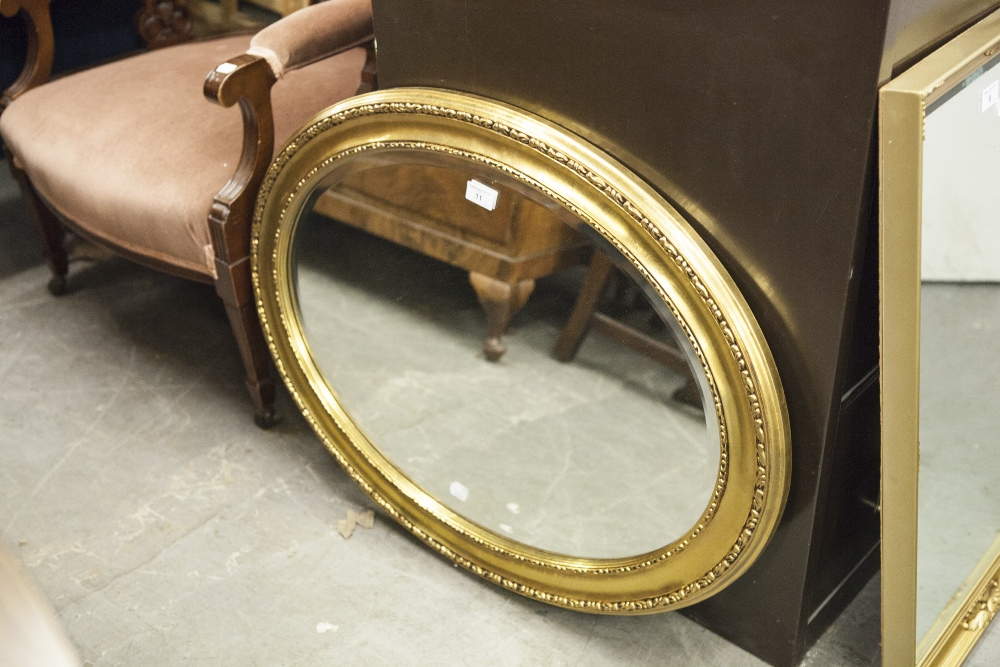 Lot 11 - AN OVAL BEVELLED EDGE WALL MIRROR, IN GILT CAVETTO FRAME