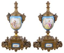 A pair of Sevres style porcelain and gilt metal urns
