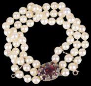 A three row cultured pearl bracelet with garnet set clasp