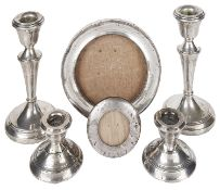 Two pairs of silver candlesticks and silver photograph frames