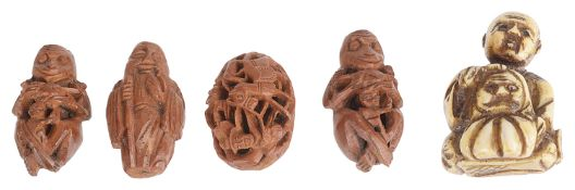 A small late 19th century Japanese carved netsuke and four coquilla nut carvings