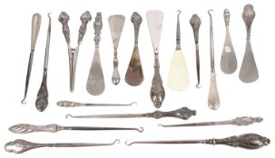 A collection of Victorian and later silver handled button and boot hooks, shoe horns