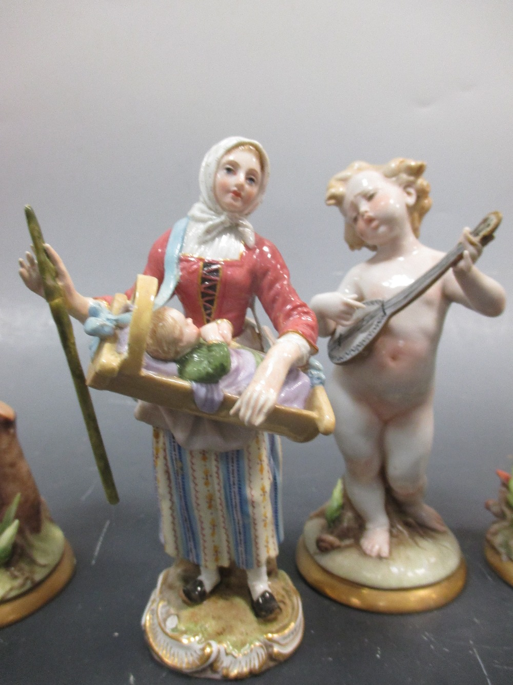 Lot 23 - A Meissen figure of a lady carrying a small baby in a crib, Two small Royal Copenhagen animalier