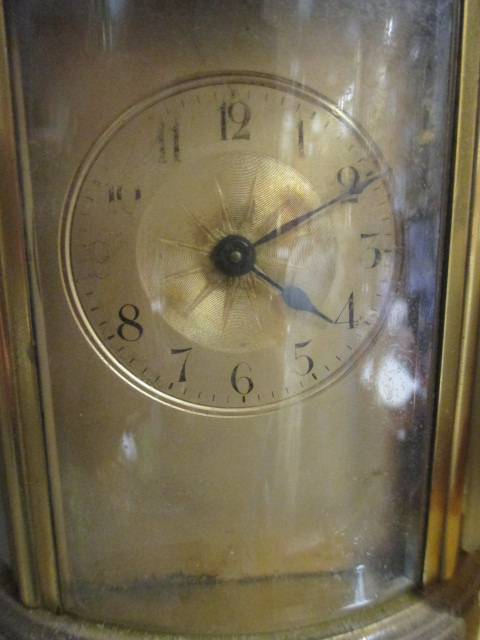 Lot 43 - An Edwardian gilt carriage clock, the glazed oval body with swing handle, Arabic numerals complete