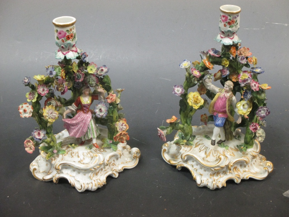 Lot 30 - A pair of Dresden porcelain figural chamber sticks with floral bocage (2)