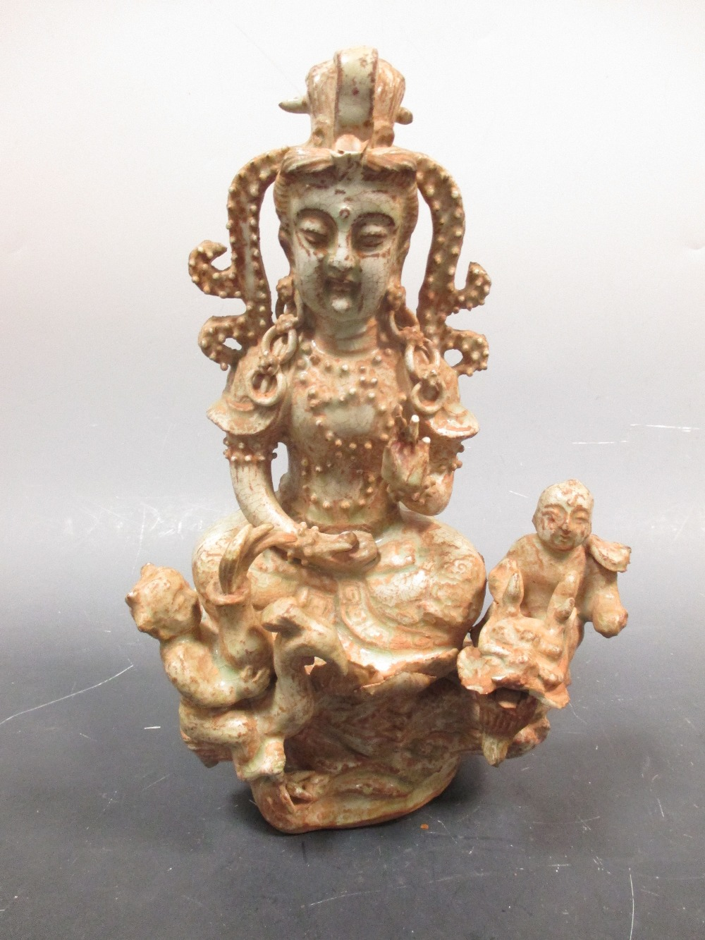 Lot 15 - A Chinese celadon glazed group of Guanyin and two attendants