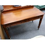 An early Victorian mahogany side table, 19th Century, with a raised back over two drawers on lotus