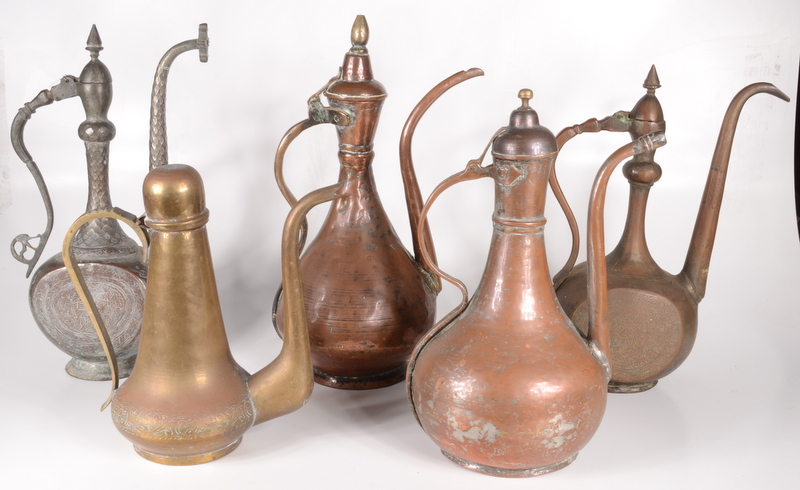 Lot 22 - Five Islamic copper and brass ewers, 18th/19th century, one decorated with rabbits amongst foliage,