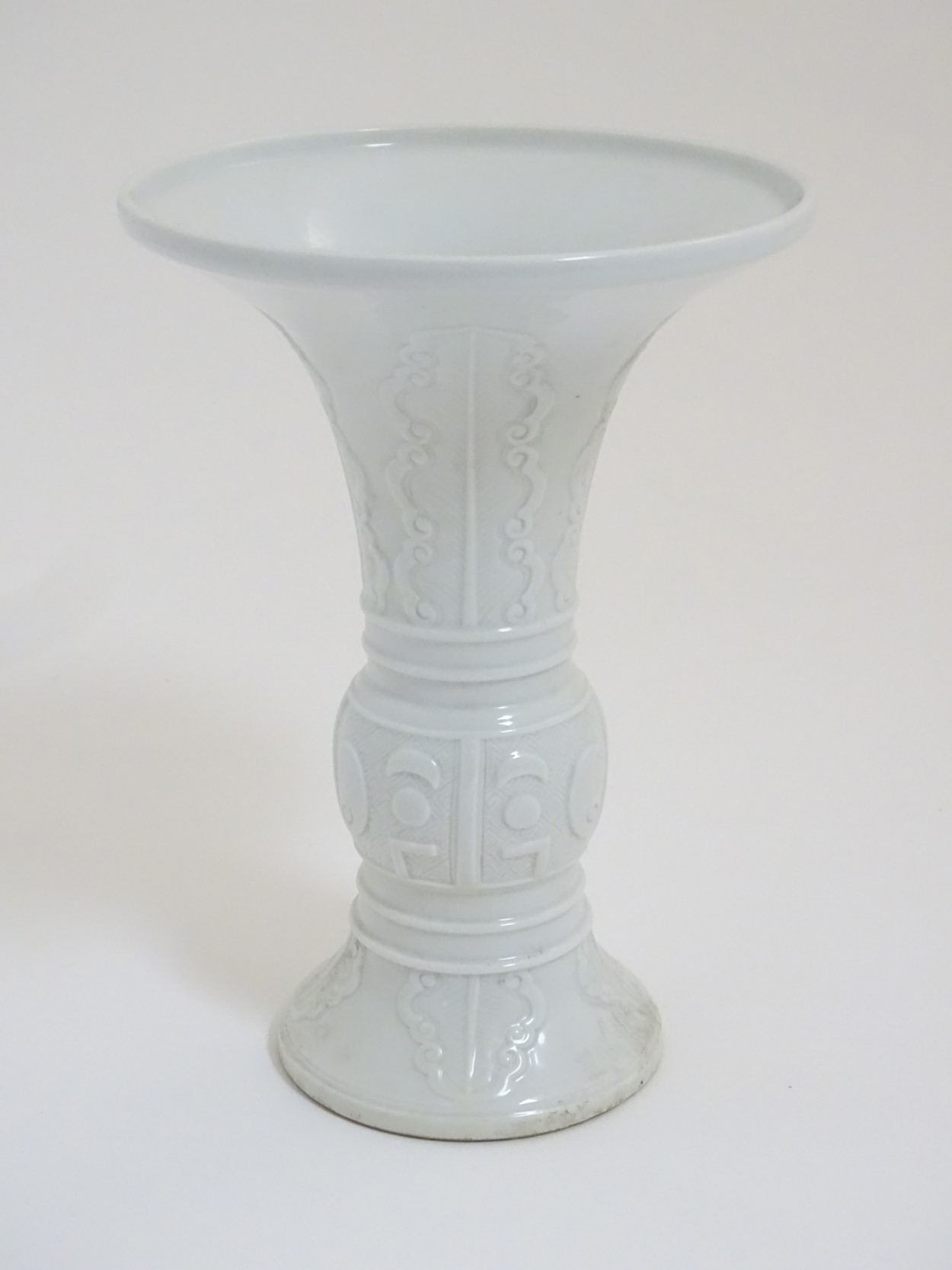 Lot 5 - A Chinese white glazed Gu vase of archaic bronze design,