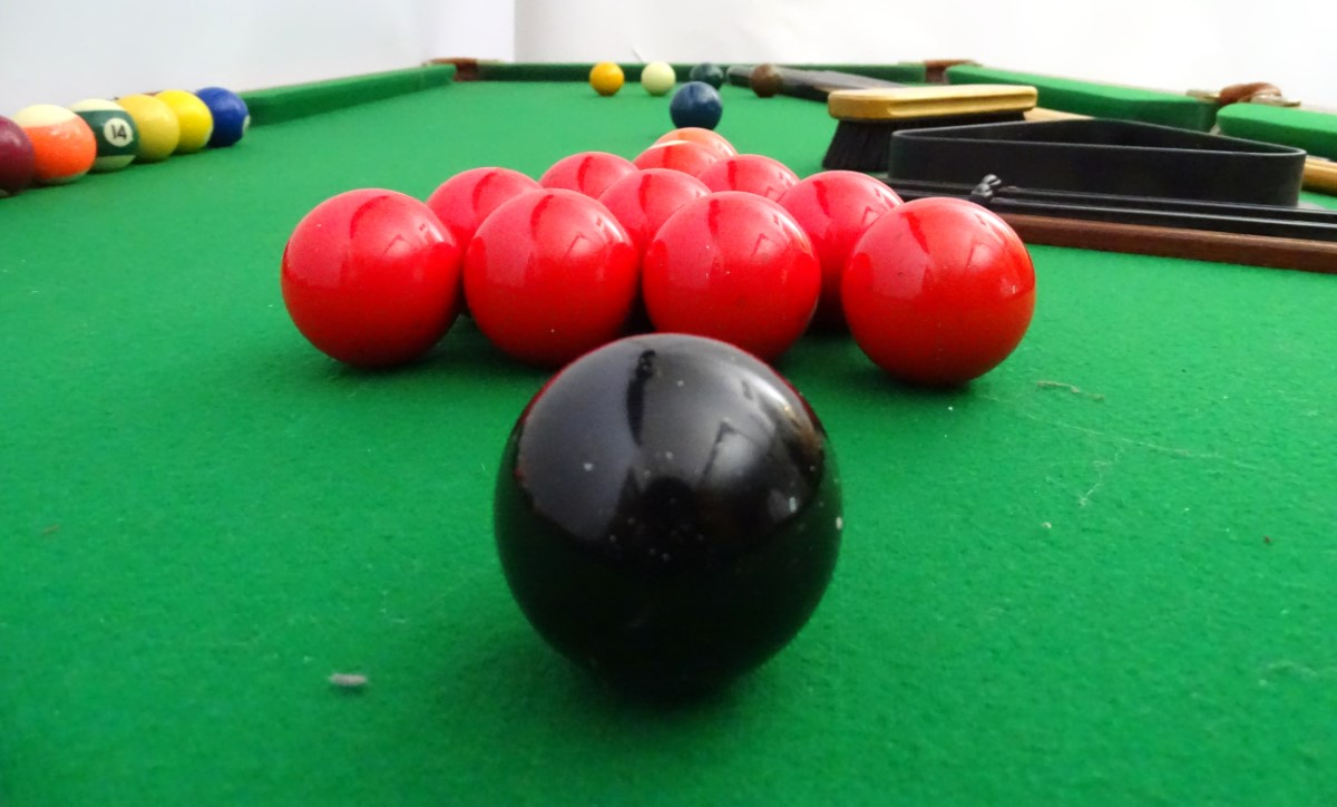 Lot 32 - A portable cue-sports table, with green baize top, together with six cues, a boxed set of snooker,