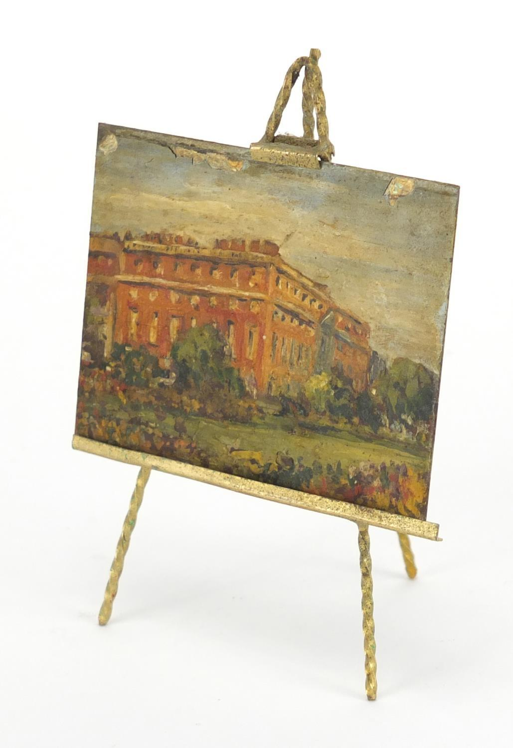 Lot 47 - Novelty brass easel housing a brass panel hand painted with Hampton Court Palace, overall 10.5cm