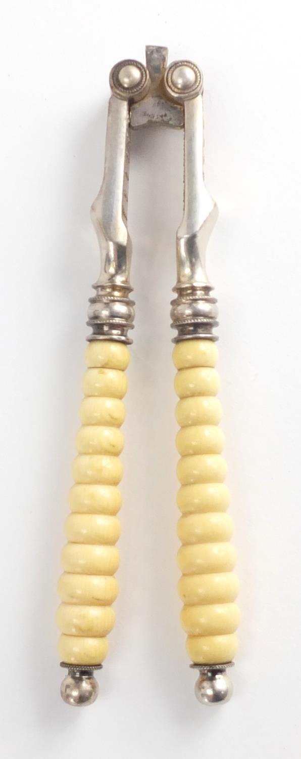Lot 56 - Set of six Victorian silver plated nut crackers with turned ivory handles, housed in a silk and