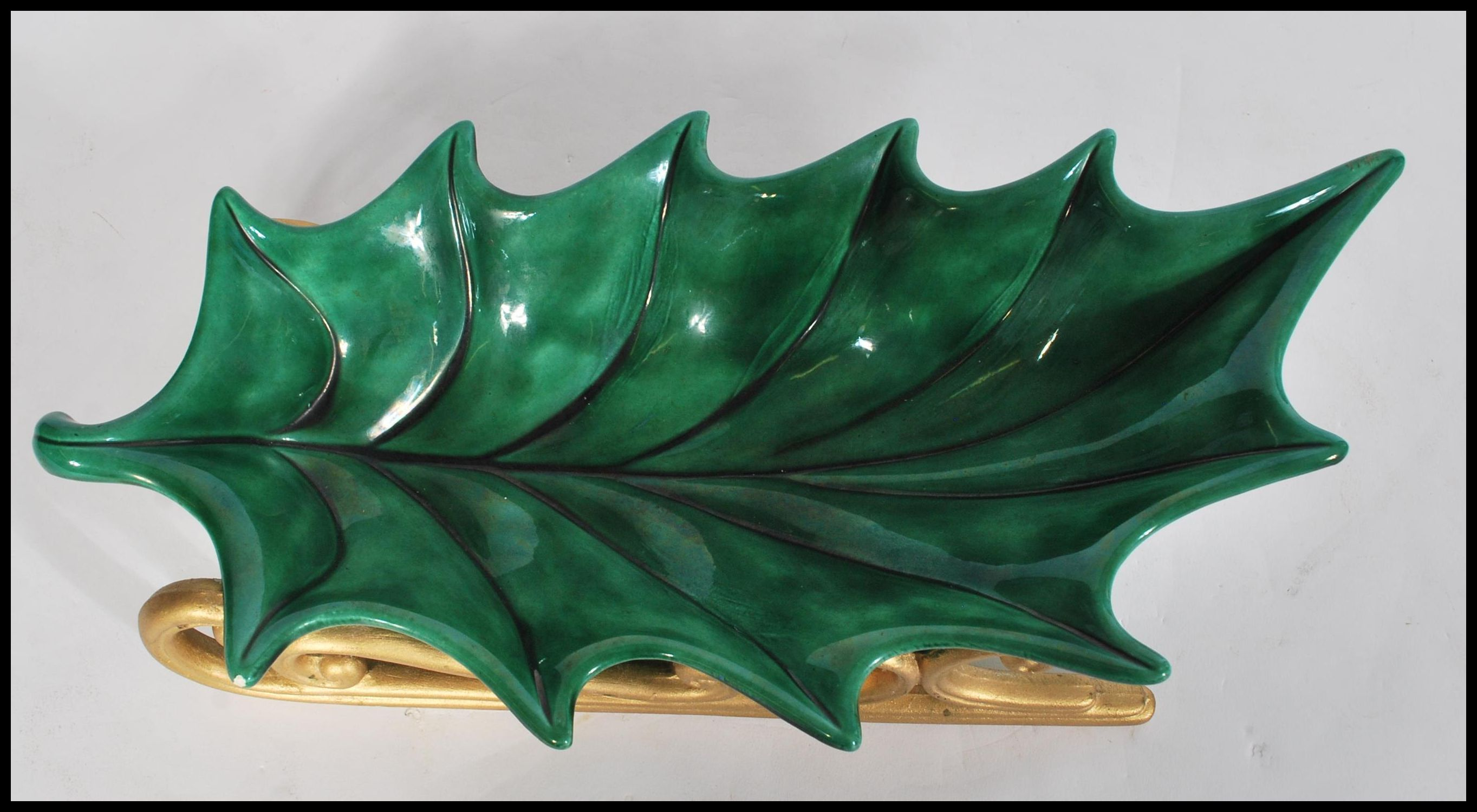 Lot 53 - A vintage 20th century ceramic Christmas decoration in the form of a large holly leaf raised on gilt