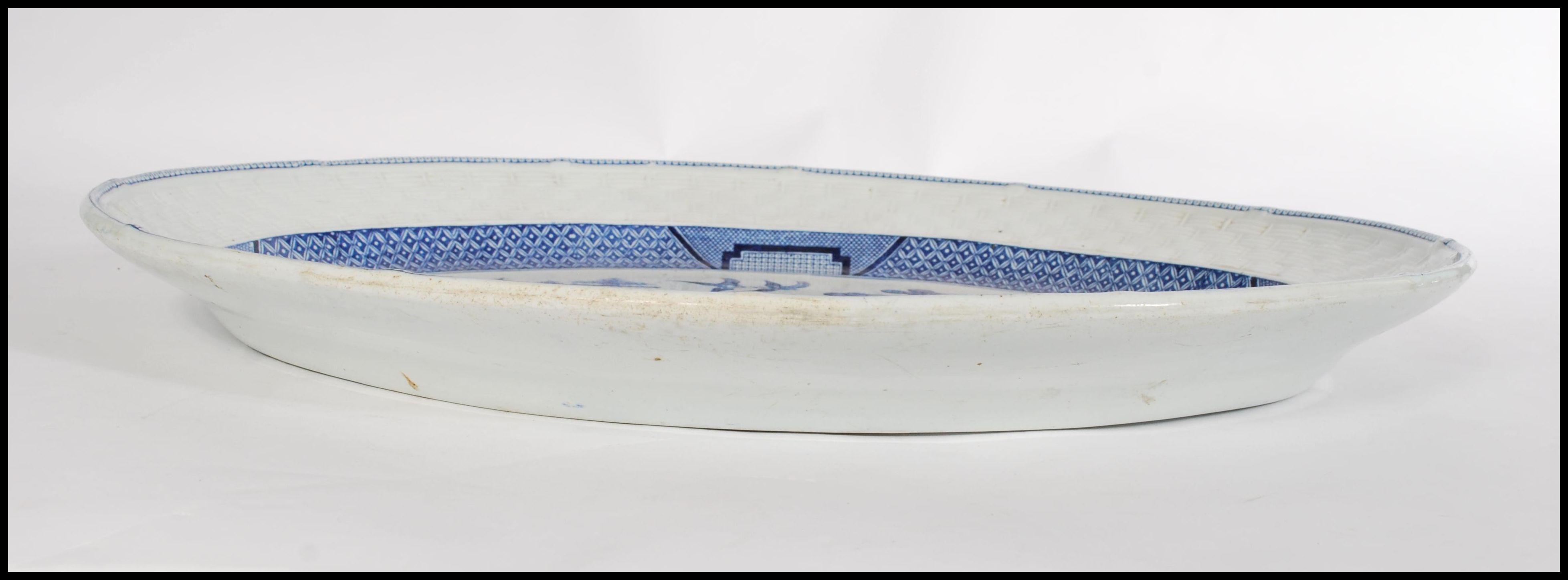Lot 32 - A 19th century Chinese blue and white willow pattern meat platter of large form having woven