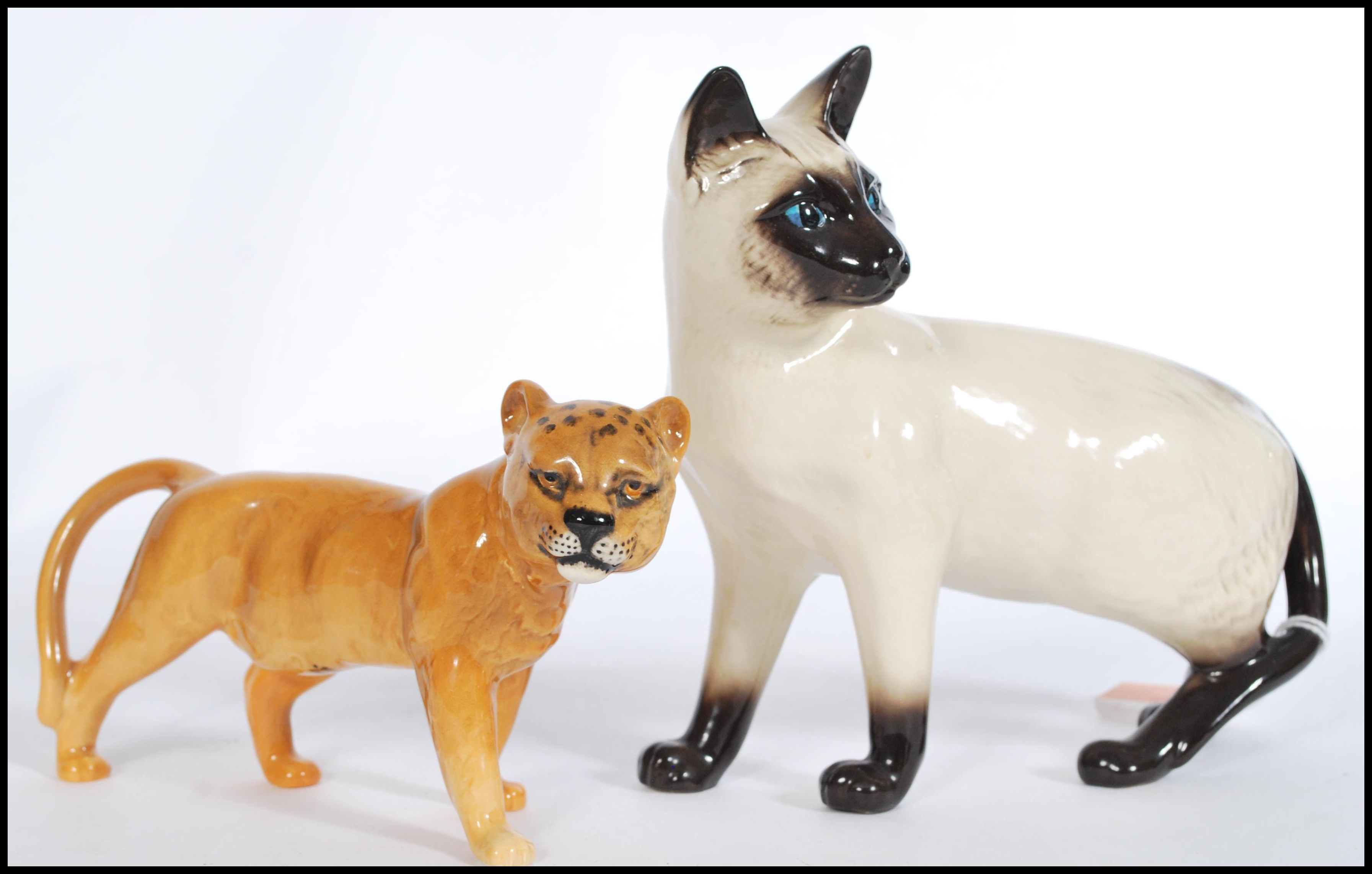 Lot 2 - A vintage Beswick ceramic figure modelled as a lioness along with a Royal Doulton figurine of a cat.