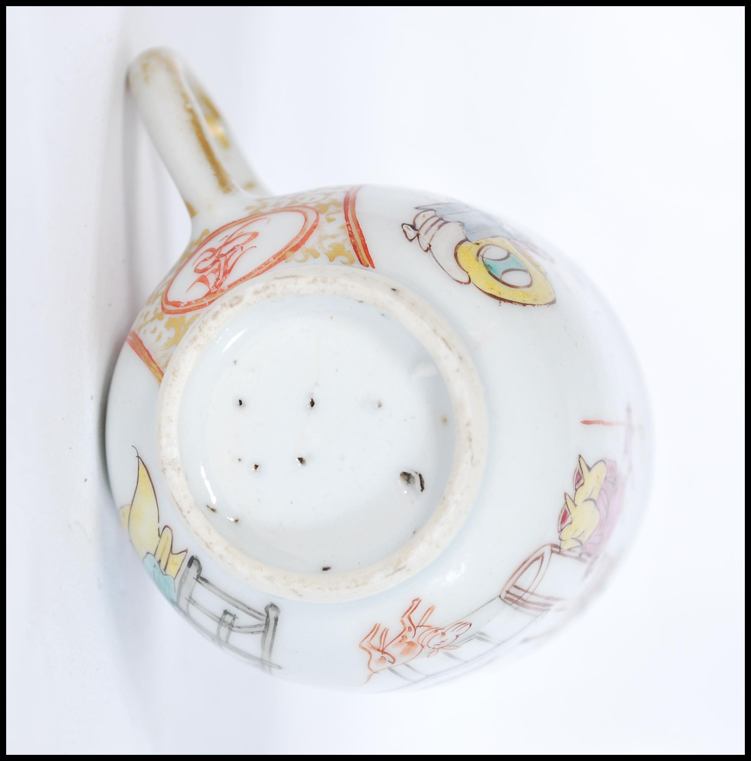 Lot 46 - An 18th century Chinese porcelain teacup depicting traditional domestic scenes with gilt and ocher