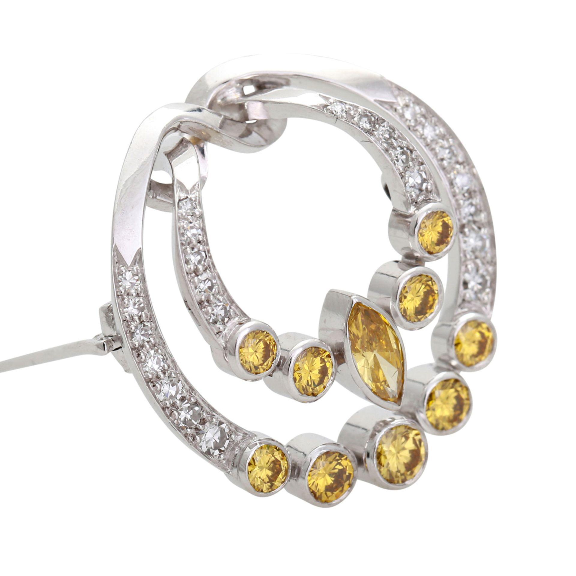 Los 21 - Brosche mit fancy gelben u. weißen Diamanten. WG 18K, in Form einer Fibel, 9 Brillanten u. 1 Diamant