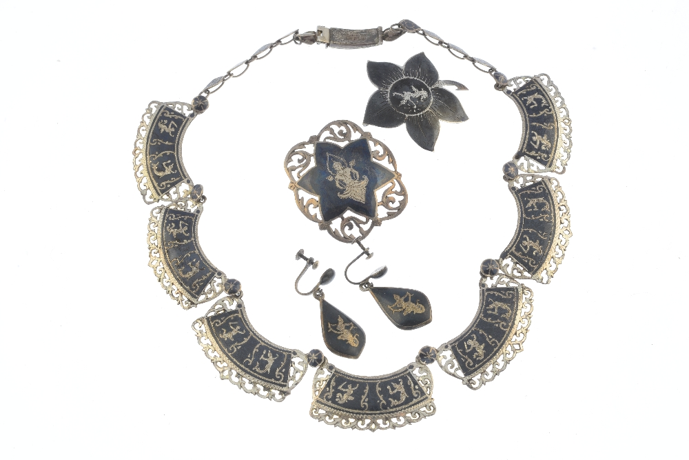 Lot 5 - Four items of Siam silver and white metal jewellery. To include a niello necklace featuring curved
