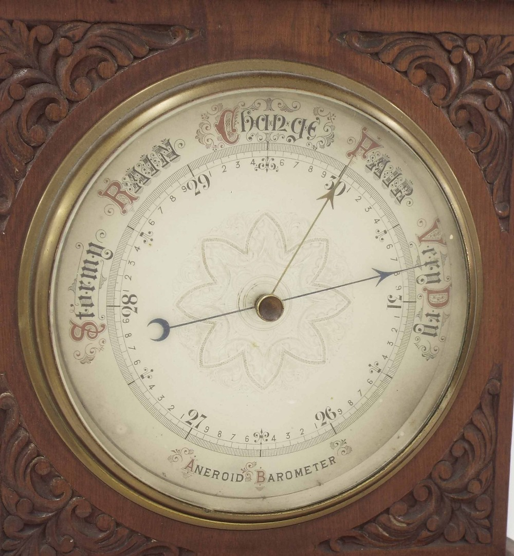 """Lot 1006 - Mahogany aneroid barometer/thermometer, the 8"""" silvered dial within a foliate carved case surmounted"""
