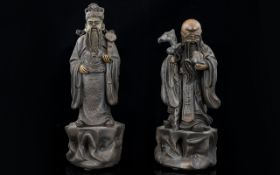 A Pair Of Oriental Figures Each in the form of Emperors, height 7 inches.