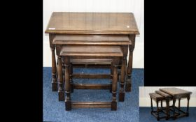 A Nest of Tables finished in varnished dark oak, of rectangular form, turned legs with rectangular
