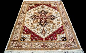 A Large Woven Silk Heriz Carpet Finley woven rug on beige ground with intricate scrolling floral and