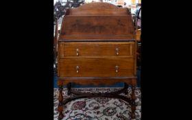 Early 20th Century Walnut Veneer Bureau raised on turned legs with carved apron detail.
