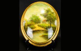 A Painted Plaster Plaque oval form convex plaque depicting a rural landscape, gilt trim, Unsigned.