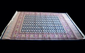 A Large Woven Silk Bokhara Carpet Ornate silk carpet with traditional lozenge and geometric repeat
