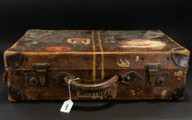 A Vintage Suitcase Brown leather top handle travel case with protective brass corners and locking