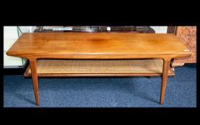 A Mid Century Style Coffee Table Rectangular table with woven cane detail to bottom stretcher and