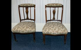 A Pair Of Mahogany Edwardian Salon Chairs. Inlaid slats, turned supports with brass castors.