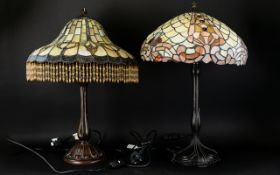 Two Tiffany Style Stained Glass Table Lamps Each raised on reproduction art nouveau cast metal