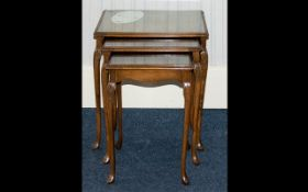 A Nest of Tables of typical form with glass inlay to tops and carved Queen Anne legs,