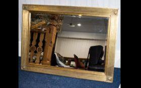 A Large Gilt Framed Bevelled Glass Mirror modern mirror in broad swept frame,