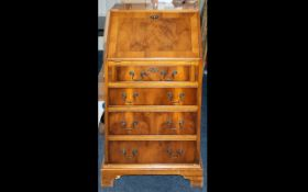 A Small Proportioned Walnut Writing Bureau Fall front with fitted interior and green leather. Four