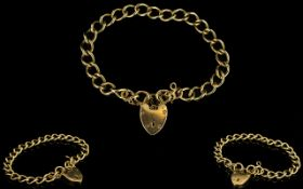 A 9ct Gold Curb Bracelet with 9ct Gold Heart Shaped Padlock - Solid construction and fully