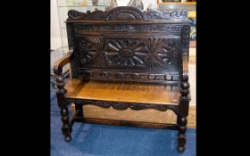 A Jacobean Style Oak Hall Bench - With carved backrest, turned supports, plank seat.